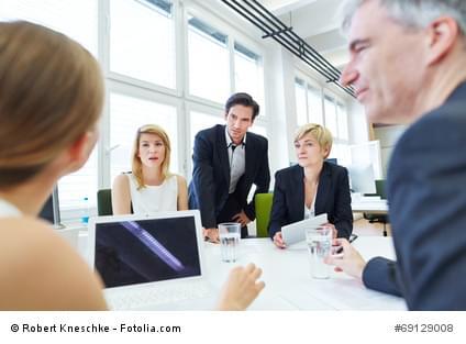 Geschäftsleute sitzen bei einer Verhandlung im Meeting um einen Tisch